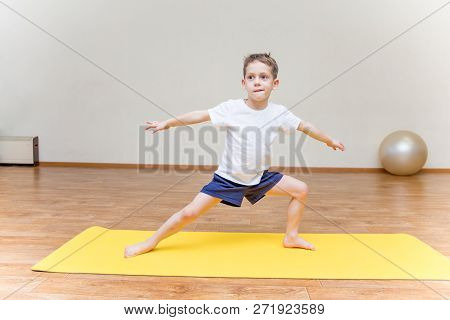 A Little Boy Practicing Yoga At Home