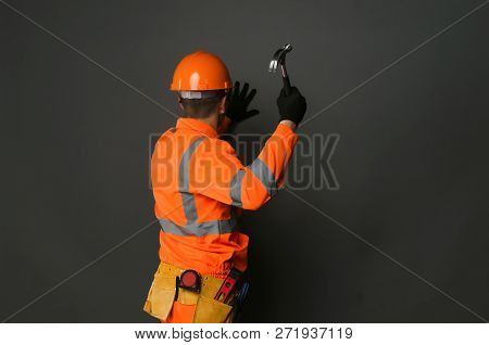 Builder Worker Is Hammering A Nail Into The Wall By The Hammer In His Hand.