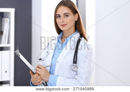 Doctor Woman Filling Up Medical Form While Standing Near Window In Hospital Office. Happy Physician