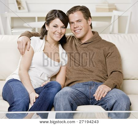 Young couple hugging on couch