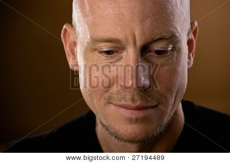 Close up studio shot of bald man with goatee and mustache looking down poster