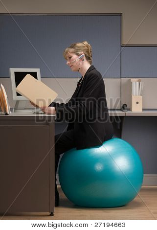 Businesswoman in headset looking at file folder while sitting on exercise ball at desk in cubicle
