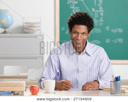 Happy teacher grading papers in school classroom