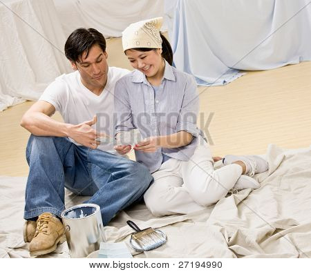 Couple sitting with paint can and color swatch preparing to decorate home interior