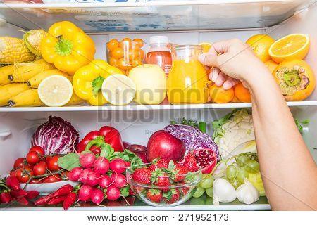Someone Picking Fruit Juice On Full Fridge