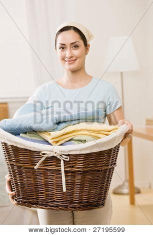 Housewife holding full basket of laundry