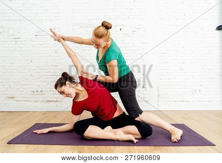 Attractive Woman And Yoga Coach Helping Her Practicing Yoga Exercise In Healthy Lifestyle Concept