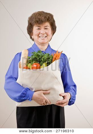Confident woman holding grocery bag full of fresh wholesome fruits and vegetables
