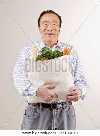 Confident man holding grocery bag full of fresh wholesome fruits and vegetables