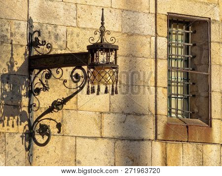 Old Wrought Iron Lamp And Window With Security Bars On The Stark Wall Of The Convent Of San Paio De