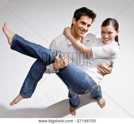 Happy barefoot man romantically carrying wife in his arms