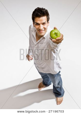 Confident barefoot man holding fresh wholesome green apple