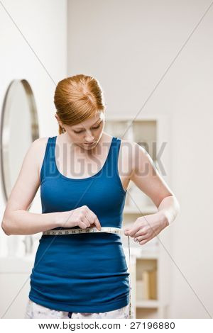 Serious woman checking dieting success by measuring her waist with measuring tape