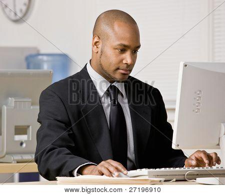 Empresario serio escribir en computadora en el escritorio