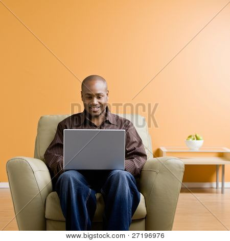 Confident man typing on laptop in livingroom poster