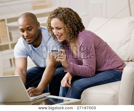 Happy couple using credit card to shop online conveniently