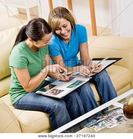 Friends sitting on sofa in livingroom looking at photograph album and remembering happy times