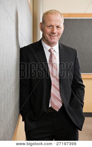 Mature businessman in full suit and tie leaning against conference room wall