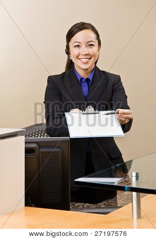 Receptionist offering clipboard and pen at front desk