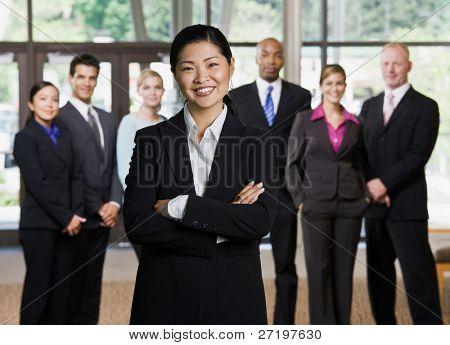 Fiduciosa imprenditrice asiatiche in posa davanti a colleghi di lavoro