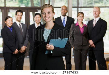 Imprenditrice fiduciosa in posa davanti a colleghi di lavoro