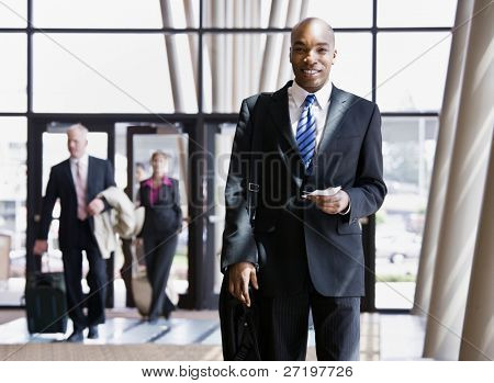 Business traveler holding briefcase, passport and airline ticket