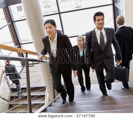 Multi-ethnic co-workers ascending and descending office stairs