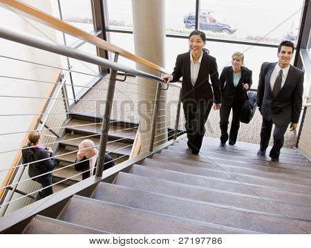 Multi-ethnic co-workers ascending office stairs