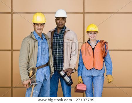 Multi-ethnic construction workers posing in hard-hats with tools