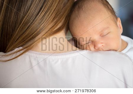 Loving Mother Cuddling Sleeping Newborn Baby Son Over Shoulder
