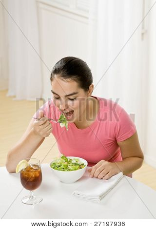 Happy woman eating wholesome, fresh bowl of salad