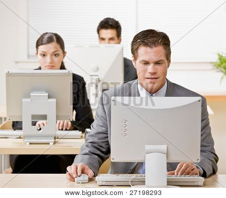 Businessman working on computer with co-workers in background poster