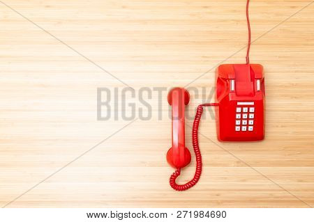 Classic Telephone On Right Corner Of Wooden Desktop, Old Red Telephone On  Wooden Desktop. Top View.
