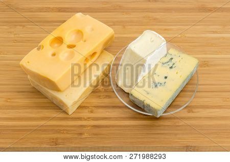 Pieces Of Blue Cheese And Brie On Glass Saucer, Medium-hard Swiss And Hard Cheese On The Bamboo Cutt
