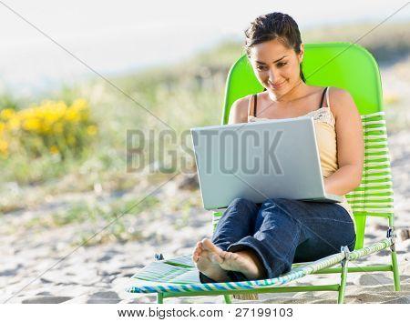 Woman using laptop at beach