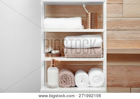 Towels, toiletries and soap dispenser on shelves in bathroom poster