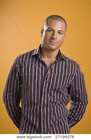 A young, attractive man is standing in an orange room, and is looking sternly at the camera.  Vertically framed shot.