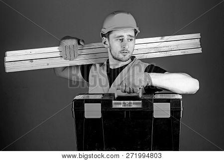 Carpenter, Labourer, Builder, Woodworker On Calm Face Carries Wooden Beams On Shoulder. Man In Helme