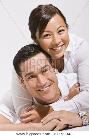 Attractive asian couple hugging with woman on top.vertical