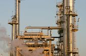 the towers and piples of an oil refinery. poster