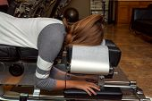 Side view of a girl laying on a tilted chiropractic table with her head face down.   There is an exercise ball in the background and she has a ponytail holder on her wrist. poster