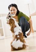 Happy woman kneeling and making video of pet dog with video camera poster