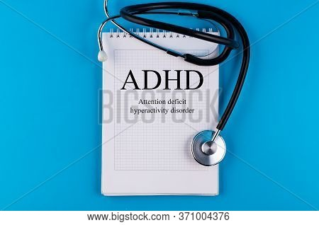 Notebook With Text Adhd - Attention Deficit Hyperactivity Disorder, On A Blue Table With A Stethosco