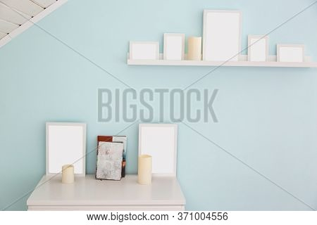 A White Shelf And A Table With White Frames For Photos, Beige Candles And Books In The Attic Room. L