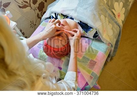 Woman Patient Lies In A Beauty Parlor. Photo Of Facial Massage Work By Beautician Hands.