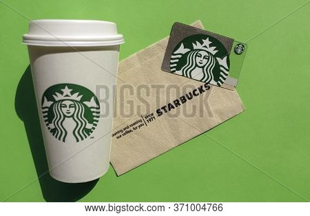 Dubai / Uae - June 7, 2020: Starbucks Gift Card And White Cup On Green Background. Top View