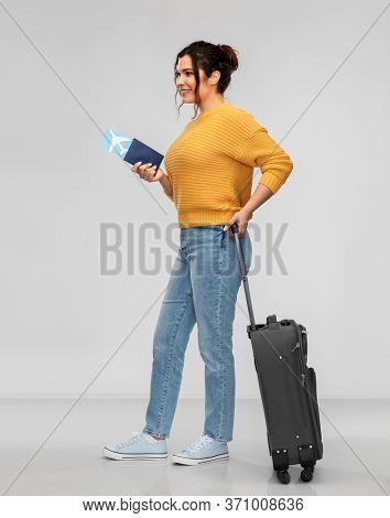 people, travel, tourism and vacation concept - portrait of happy smiling young woman with pierced nose with passport, air ticket and carry-on bag over grey background