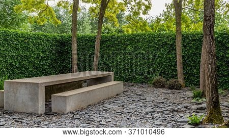 Big Concrete Picnic Bench In An Natural Forest Garden With Trees And A Hedge Enclosing The Garden