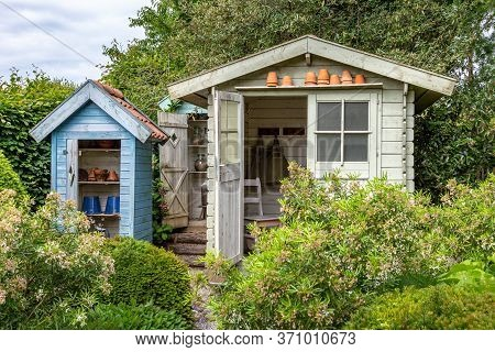 Wooden Garden Cabin And Garden Closets With Plants In The Foreground