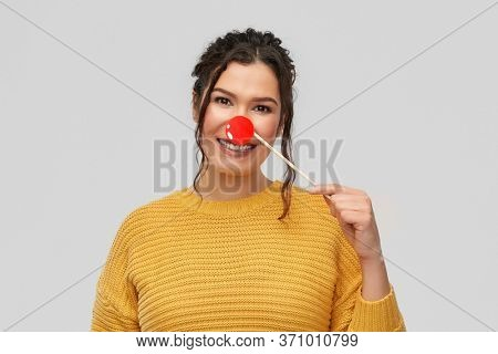 red nose day, party props and photo booth concept - portrait of happy smiling young woman with clown nose over grey background